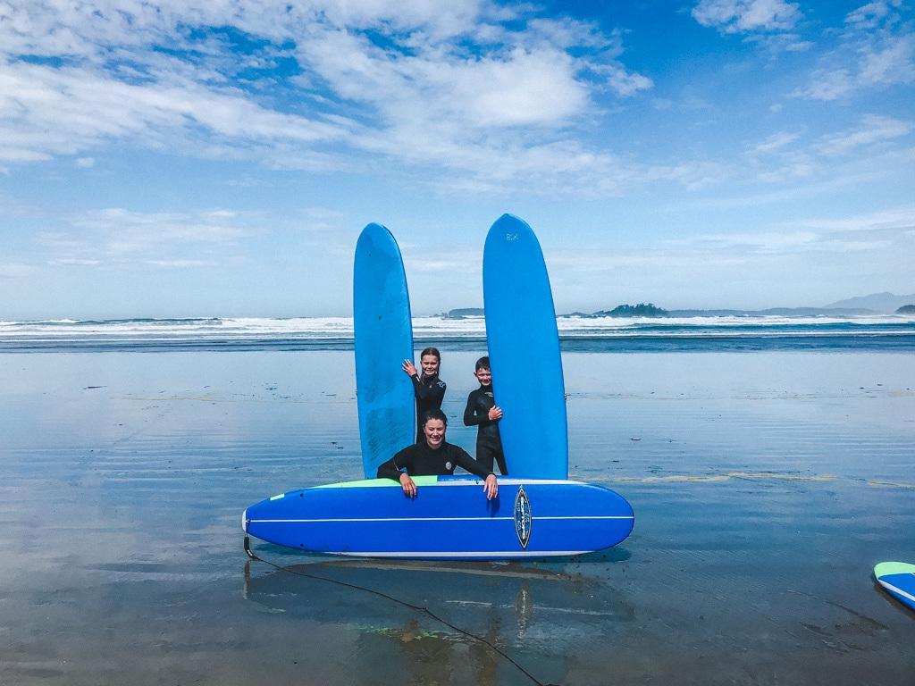 Family on beach with surfboards at the tofino surf club