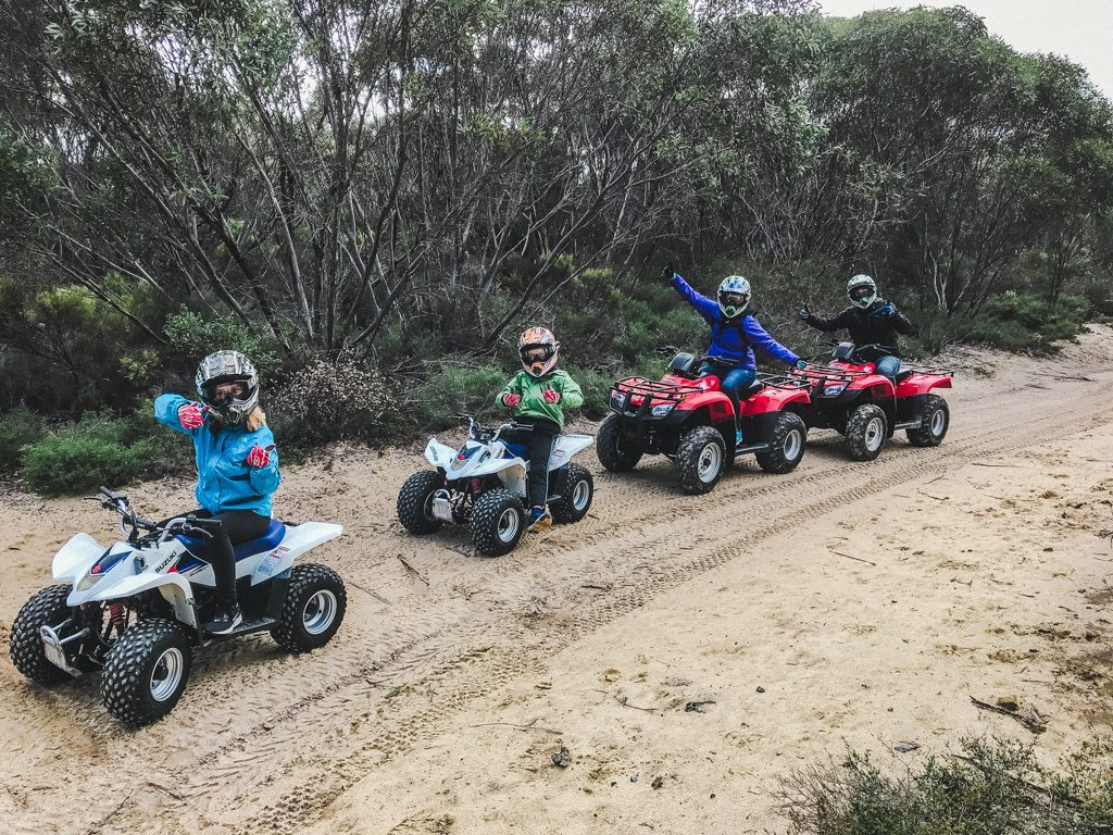 family posing for a photo while sitting on quads