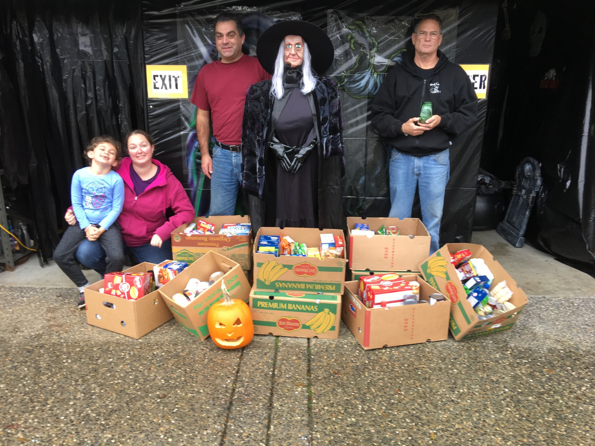 family standing outside haunted house langley with food bank donations