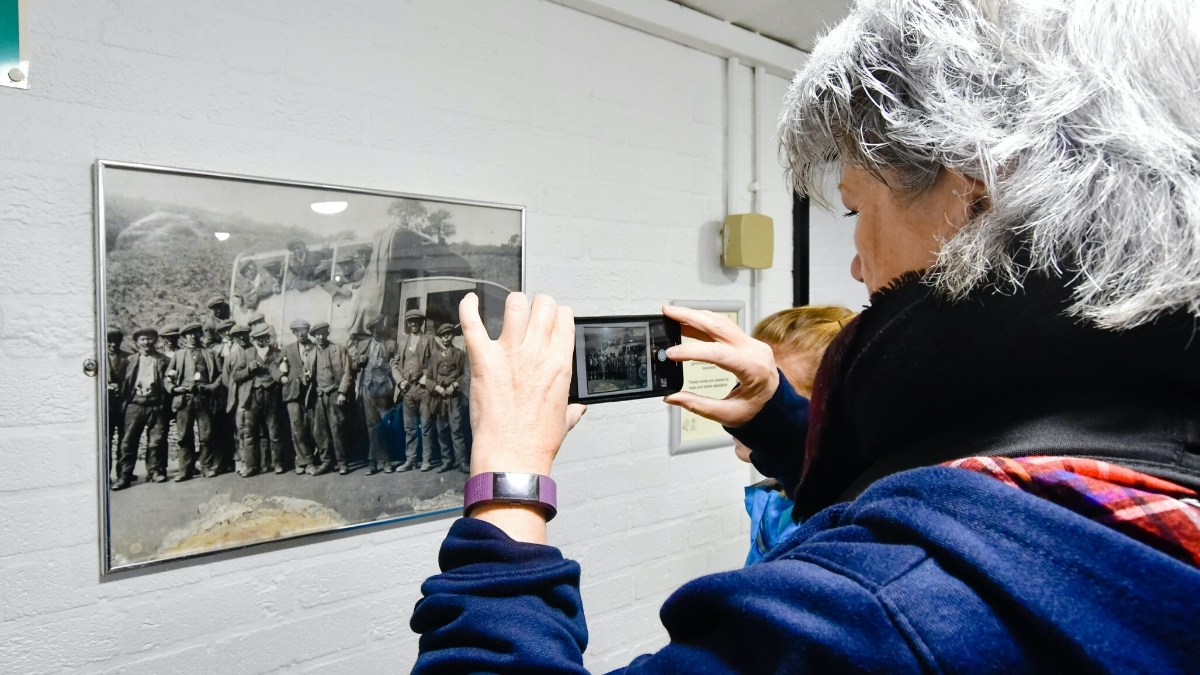woman taking a photo of a photo at big pit national coal museum