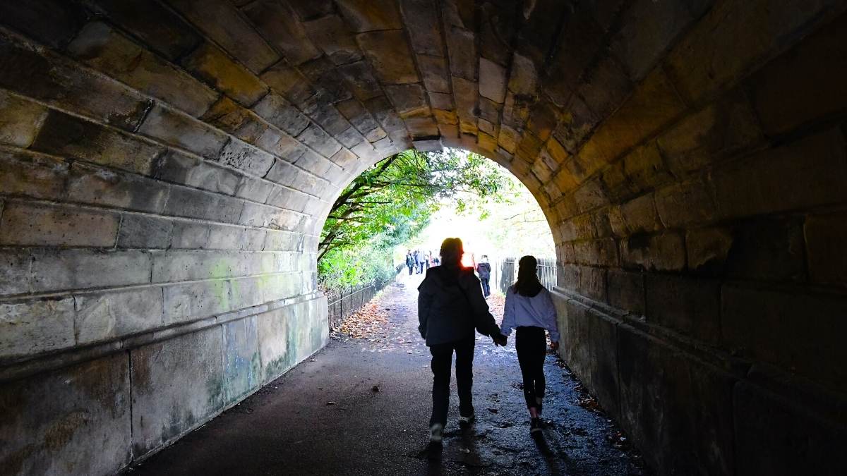 woman and child holding hands while walking through a tunnel