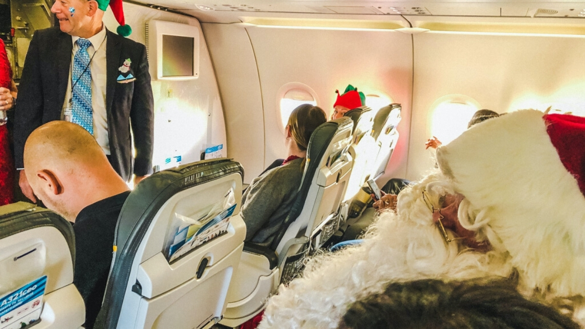 Santa sitting in airplane seat Children's Wish Flight in Search For Santa