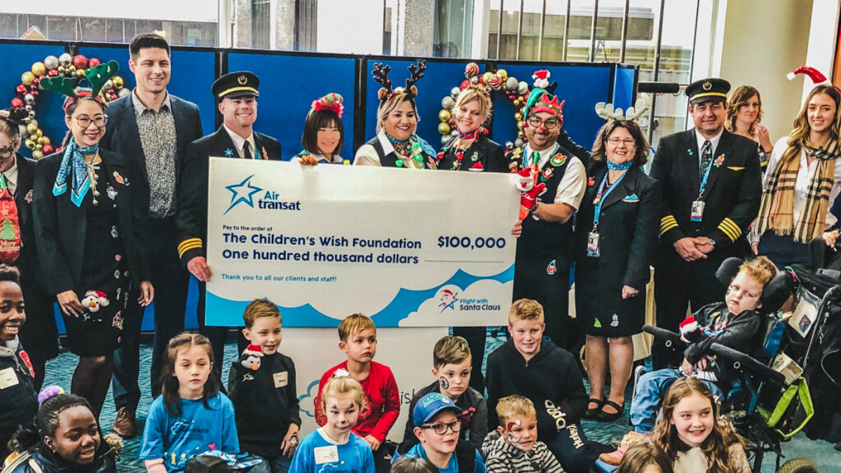 Group of people holding a large check from Air Transat worth $100,000 for Children's Wish Foundation