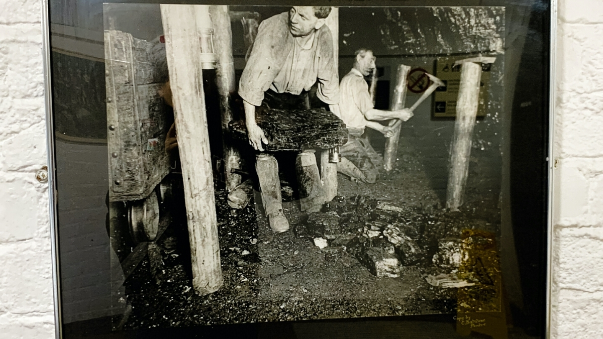 an old photograph of men working inside the big pit mine