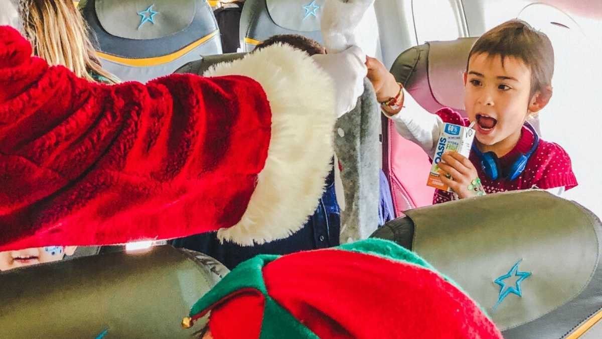 Santa handing a stocking to a child on the Children's Wish Flight in Search For Santa