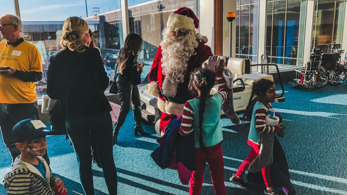 Santa greeting children as they depart the Children's Wish Flight in Search For Santa