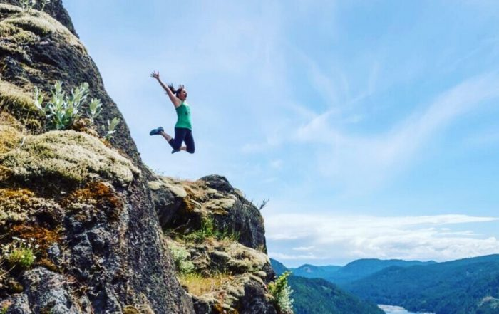 Jami Savage jumping off a mountain