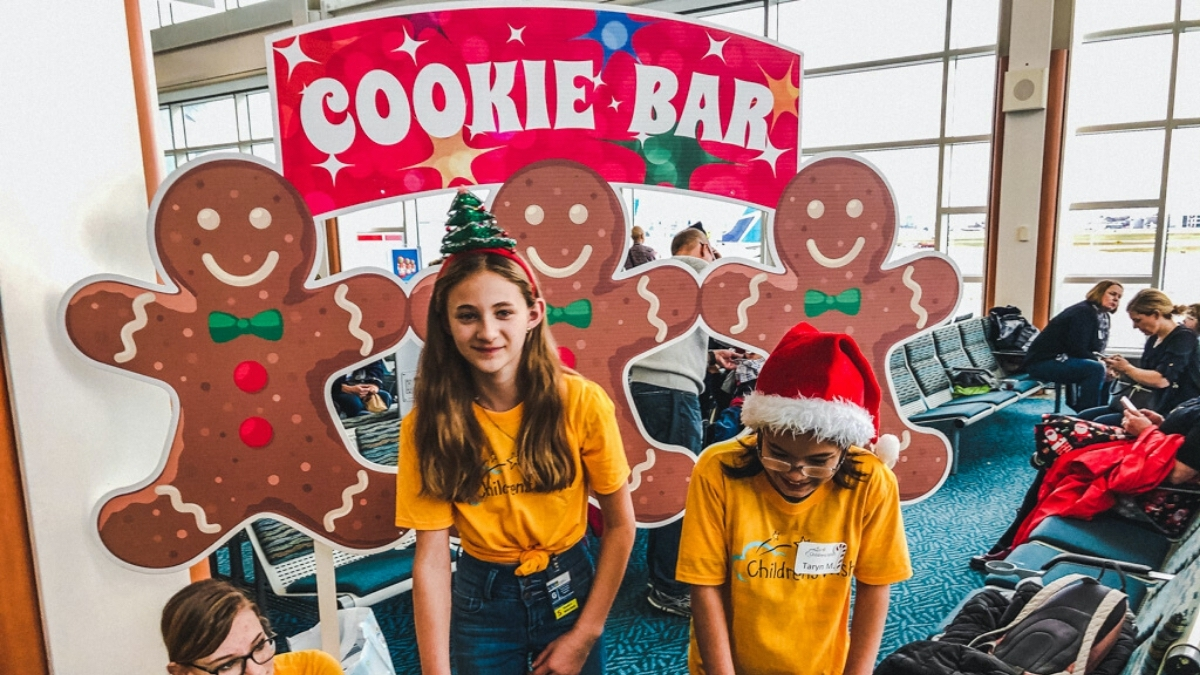 Two young girls running a cookie bar for Children's Wish Flight in Search For Santa