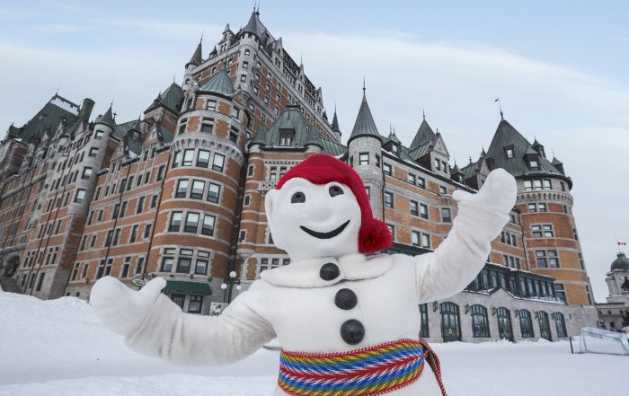 Bonhomme standing outside building in quebec city at carnaval de quebec
