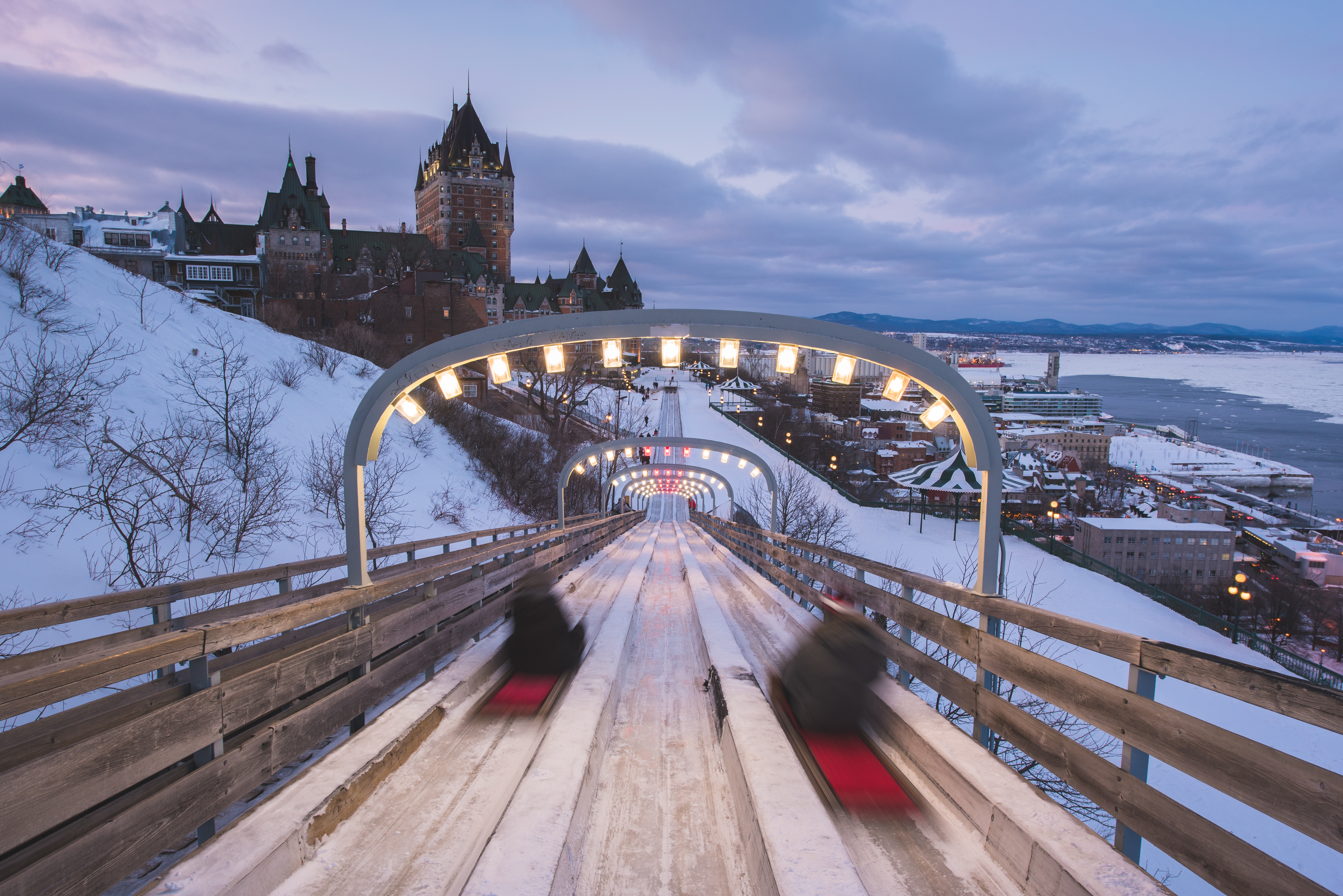 two people sliding down large snow slides at carnaval de quebec