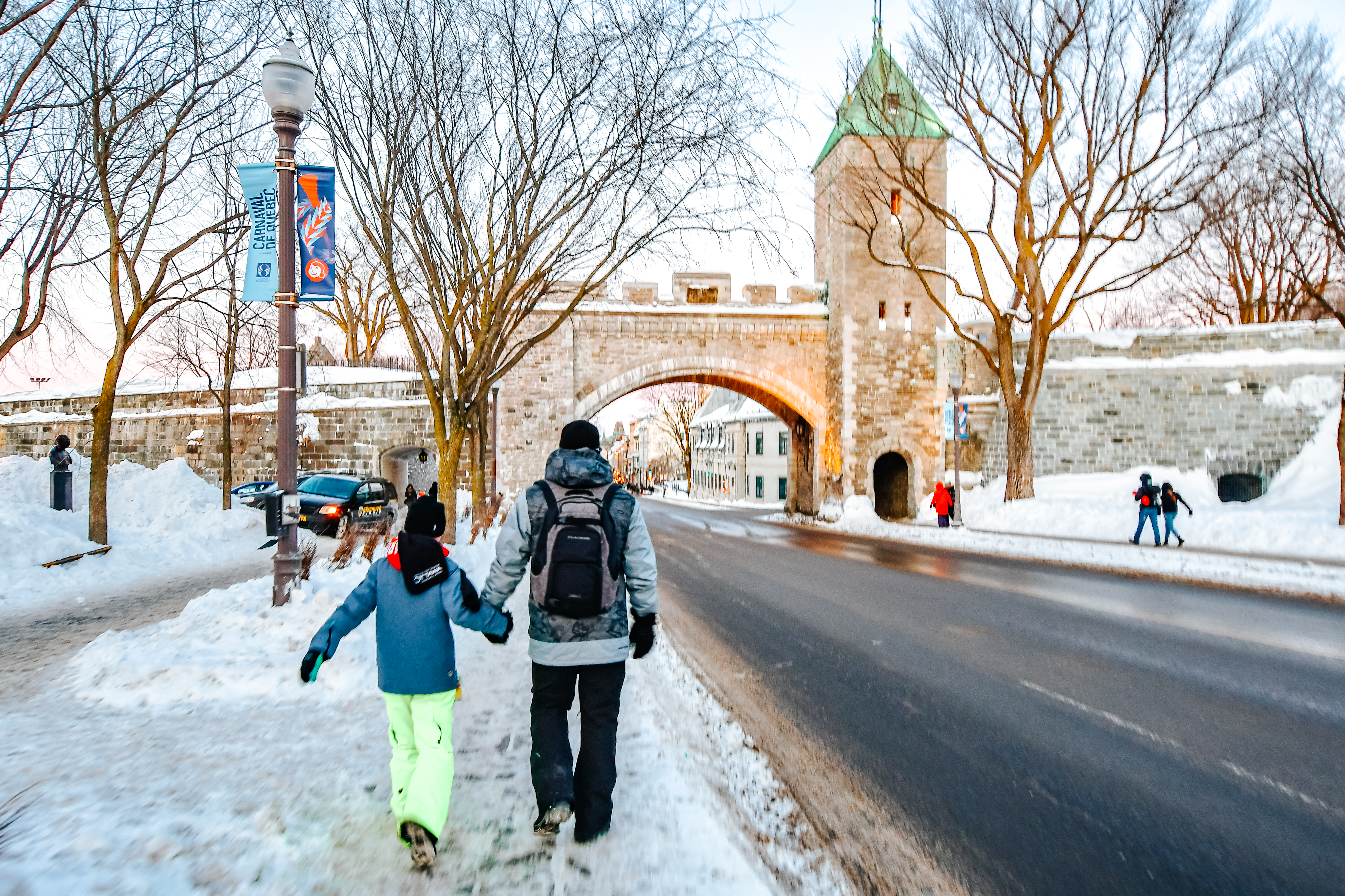 father and daughter walking towards bus stop in quebec city as they head to carnaval de quebec