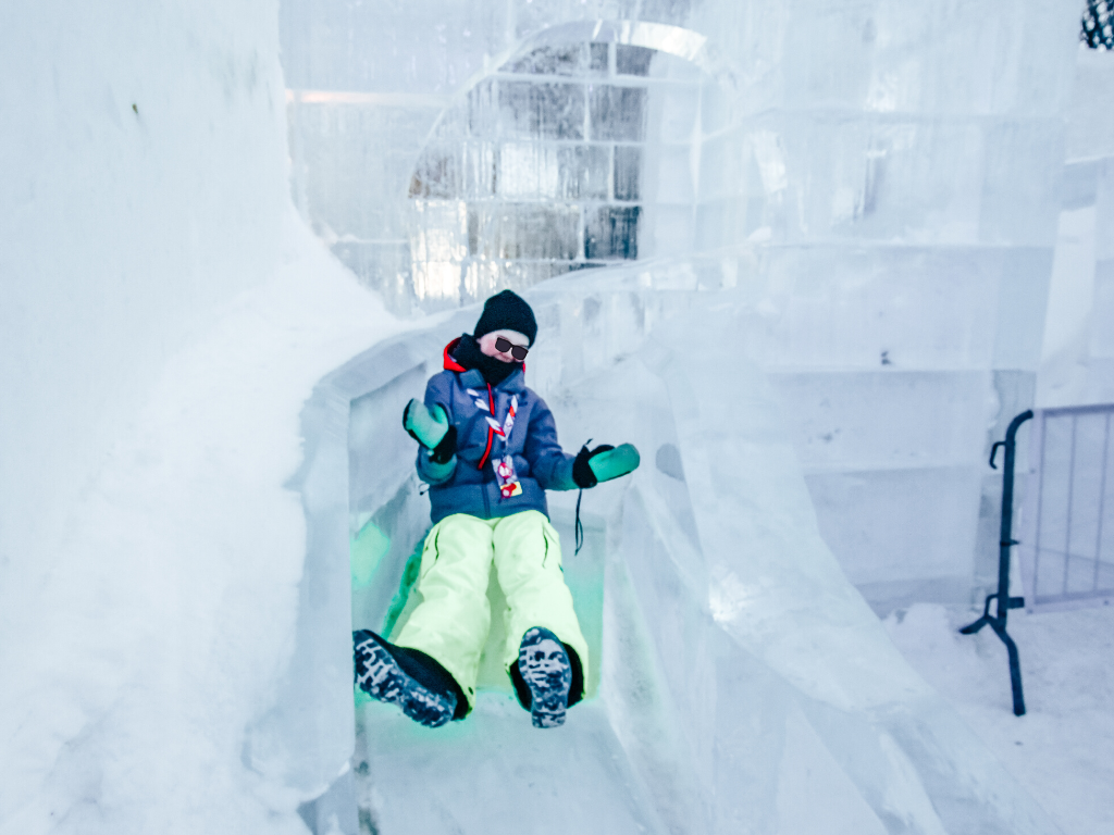 girl sliding down ice slide in bonhommes ice castle at carnaval de quebec
