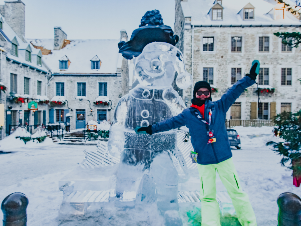 girl standing in front of a bonhomme ice sculpture at carnaval de quebec
