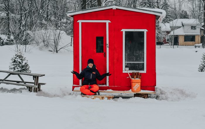 Jami Savage sitting in front of red ice fishing house in Laval