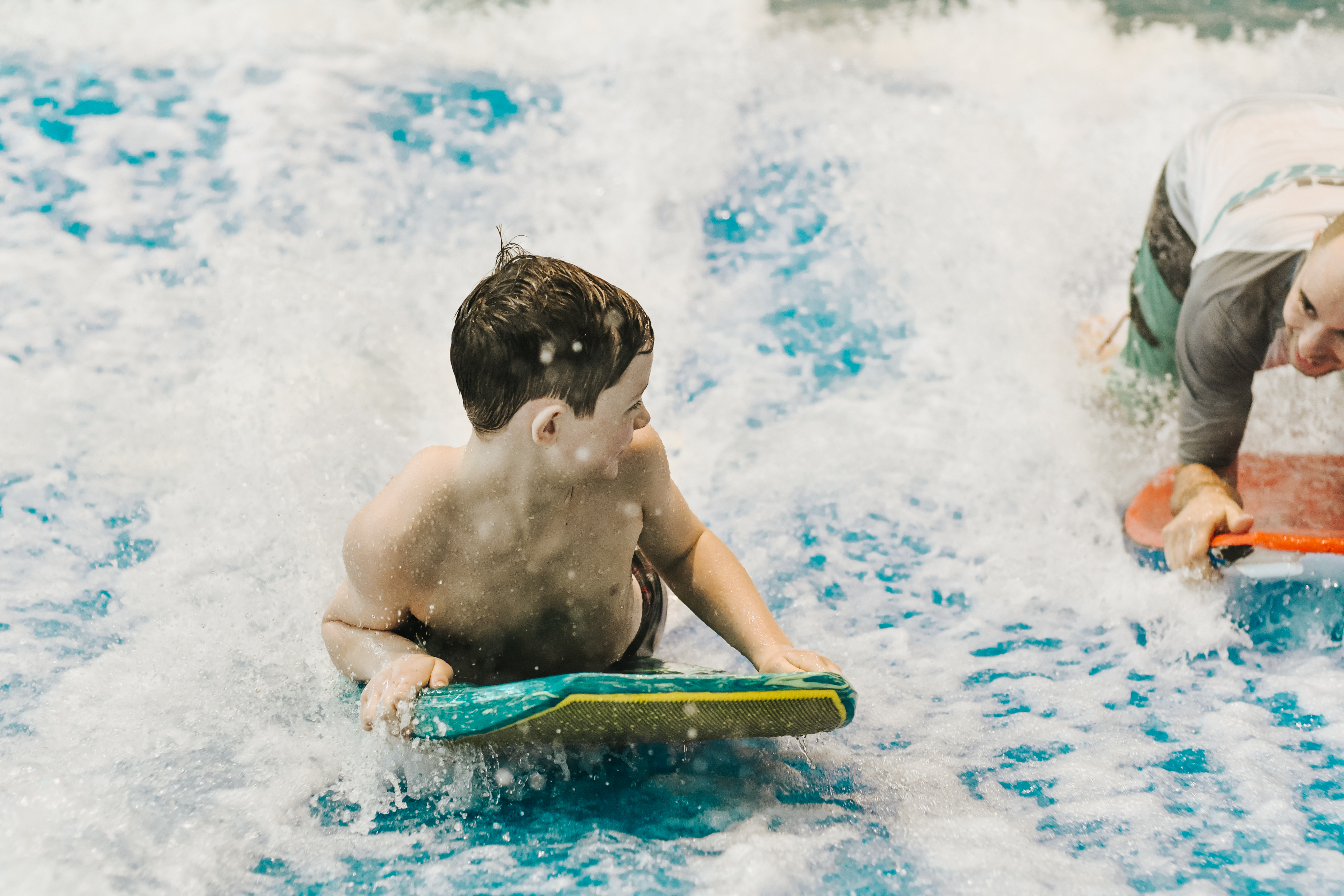 boy on surf board getting coached by an instructor at laval indoor surfing