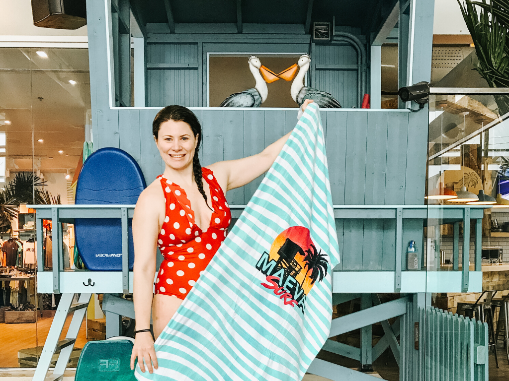 jami savage on the sidelines holding a maeva surf towel in front of the gift shop at laval indoor surfing