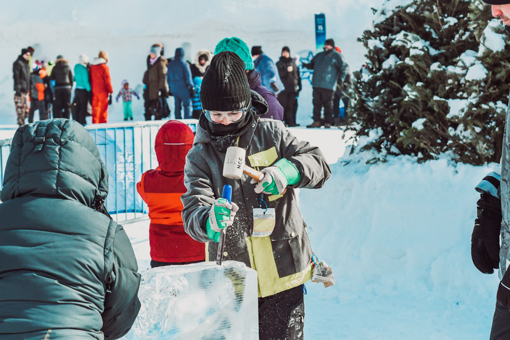 boy using a chisel and mallet on a large block of ice at winterlude guide