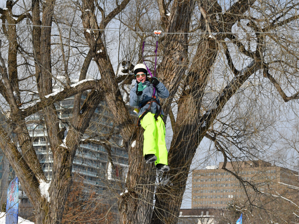 girl zip lining past the trees at winterlude guide