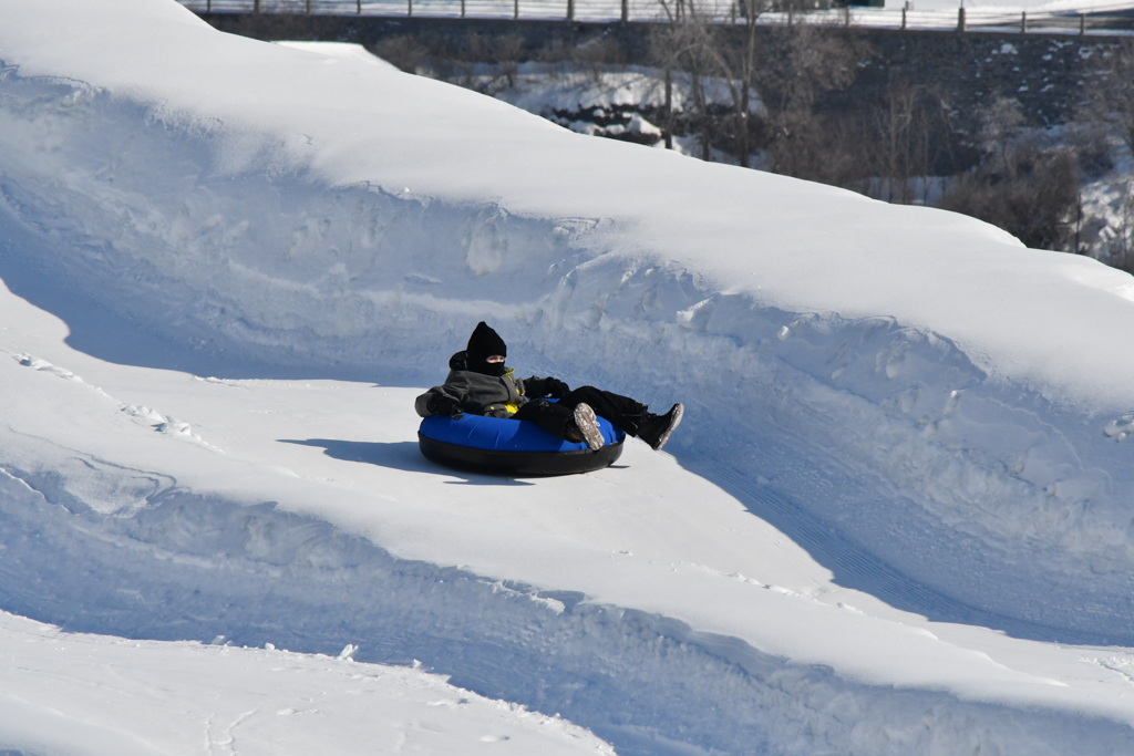 boy tubing down snow covered hill at winterlude guide