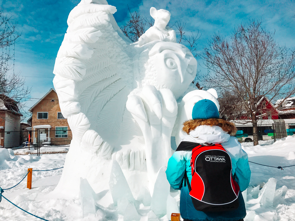 woman standing in front of giant owl snow sculpture at winterlude