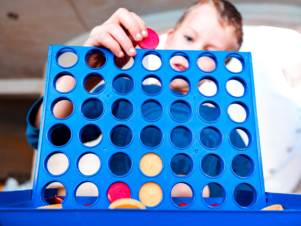 Boy playing connect four for backyard lawn games