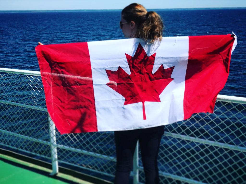 Jami Savage holding a Canadian flag for Our Stance On COVID blog