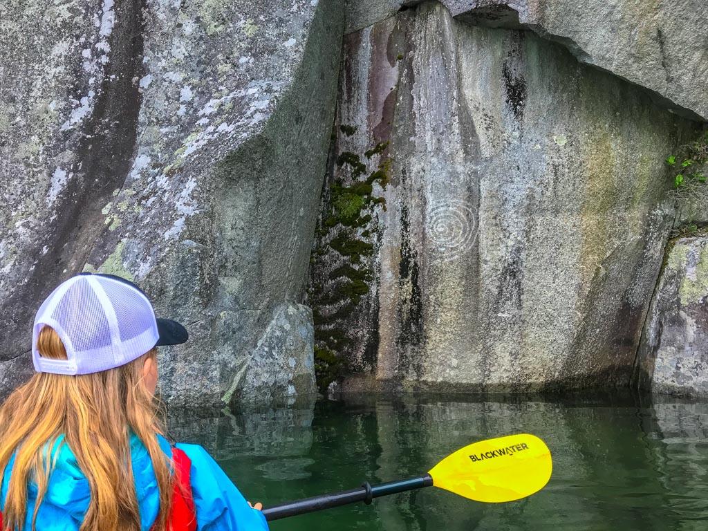 Girl looking at aboriginal pictographs during her Harrison Lake kayaking adventure