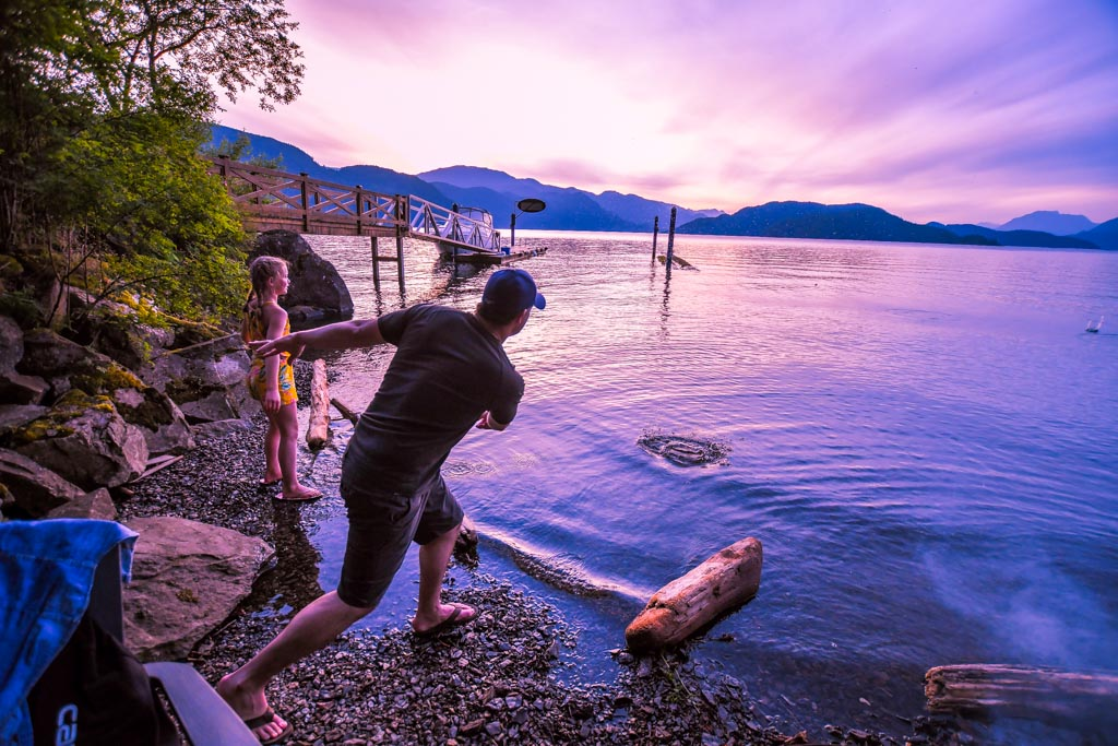 Father skipping rocks at The Lodge At Harrison Lake