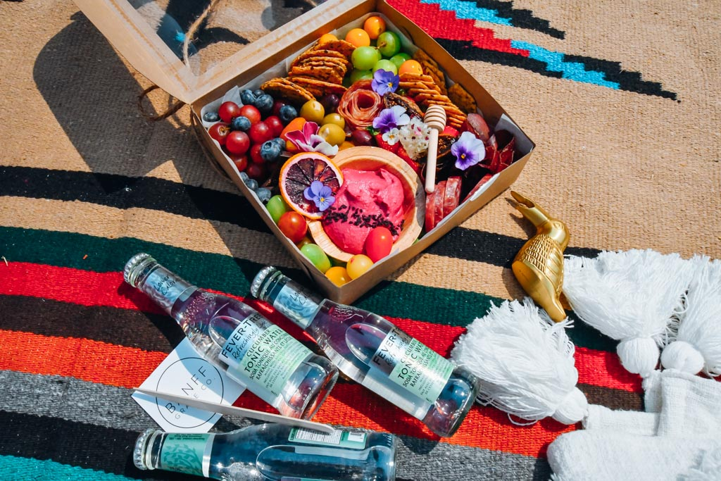 picnic blanket with graze box and drinks sitting on it