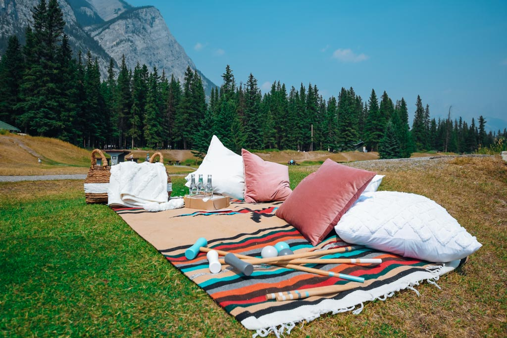 luxury picnic set up on the grass in front of a large mountain