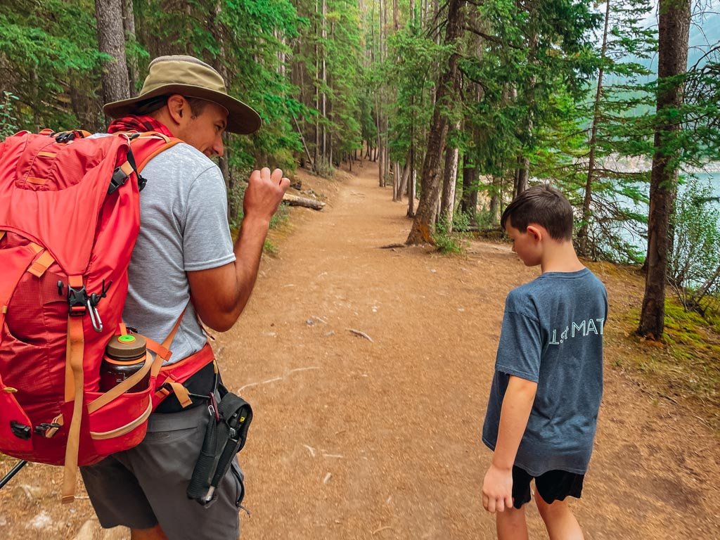 hiking guide explaining information to young boy on a trail