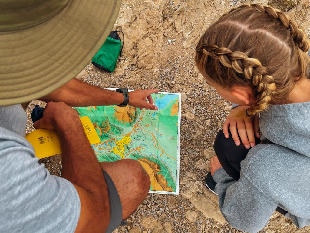 girl looking at hiking map that is held by the guide