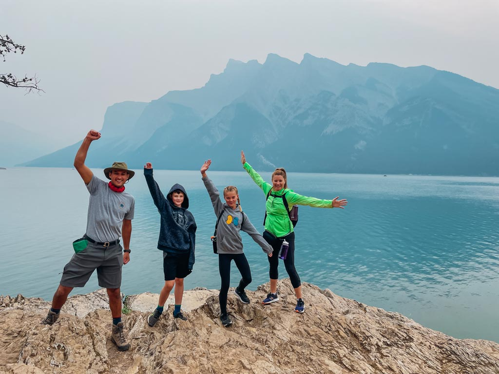 hiking guide and family standing on top of a large rock in front of a lake