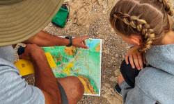 hiking guide showing a hiking map to a young girl