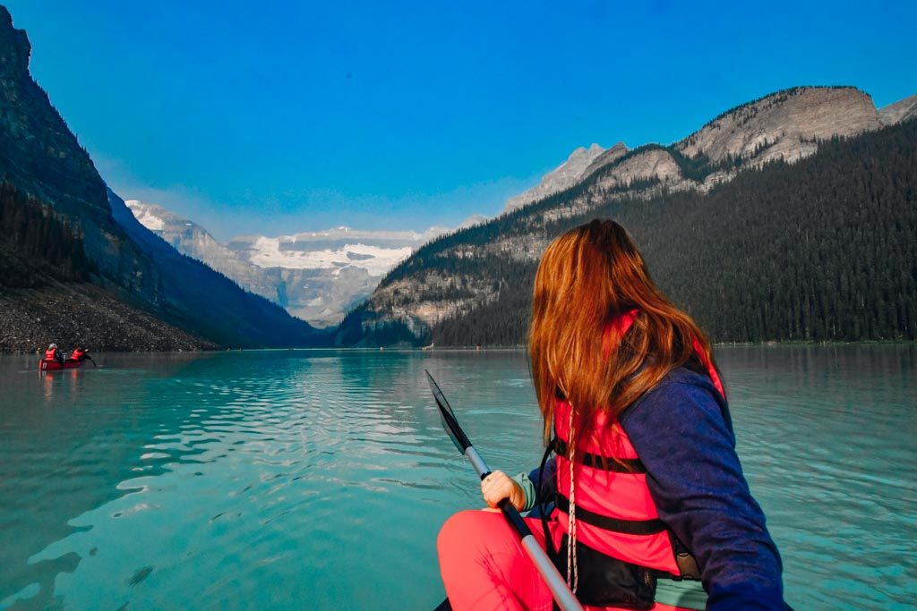 woman turned looking at the scenery behind her while sitting in a canoe on lake louise