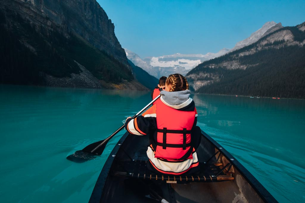 two kids paddling in a canoe on lake louise