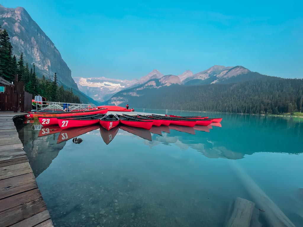 group of red canoes floating on a blue coloured lake louise with the mountains in the background
