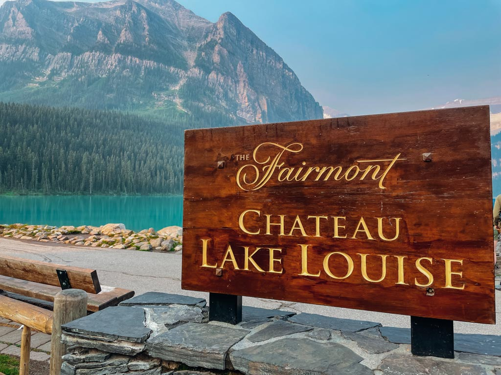 fairmont chateau lake louise sign with the lake and mountains in the background