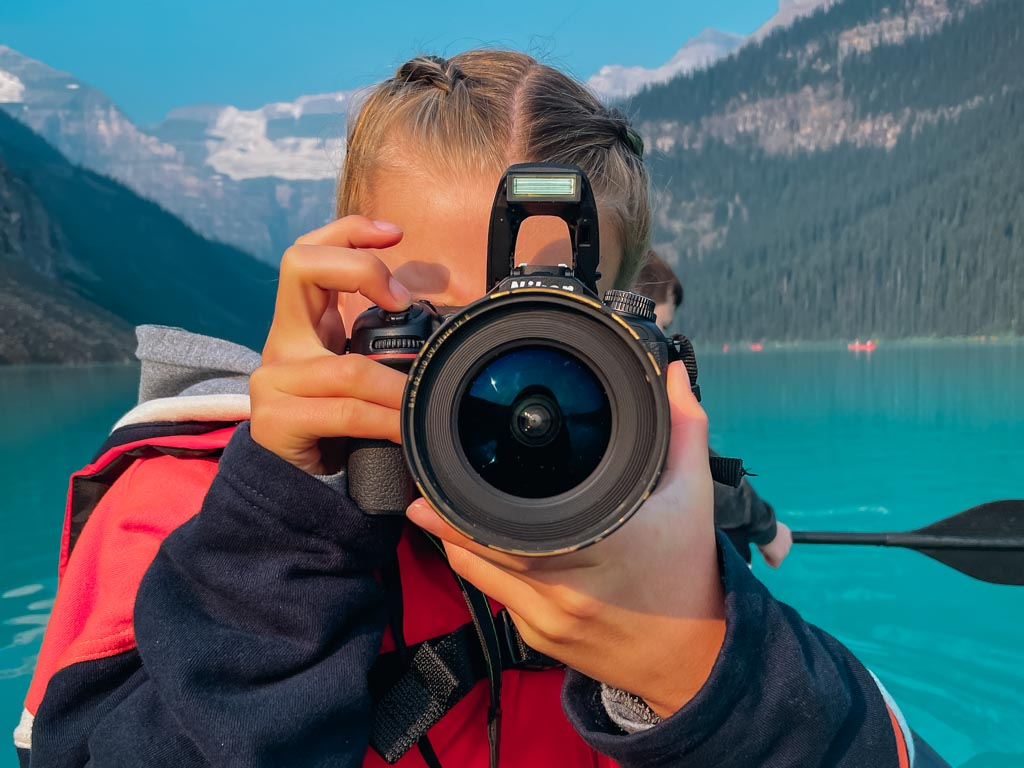 girl pointing her camera lens at the photographer with lake louise in the background