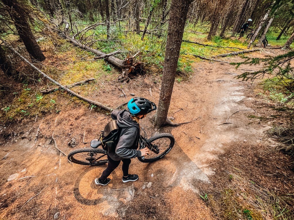 looking down at a girl walking her mountain bike on a trail