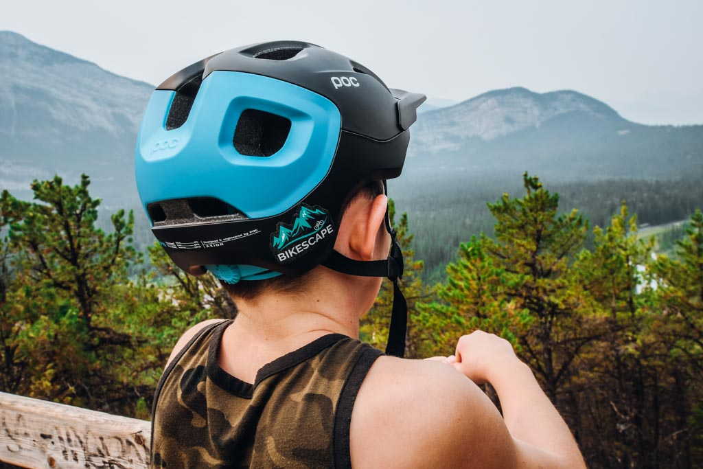 back of a boys head who is wearing a bike helmet and looking out at the views