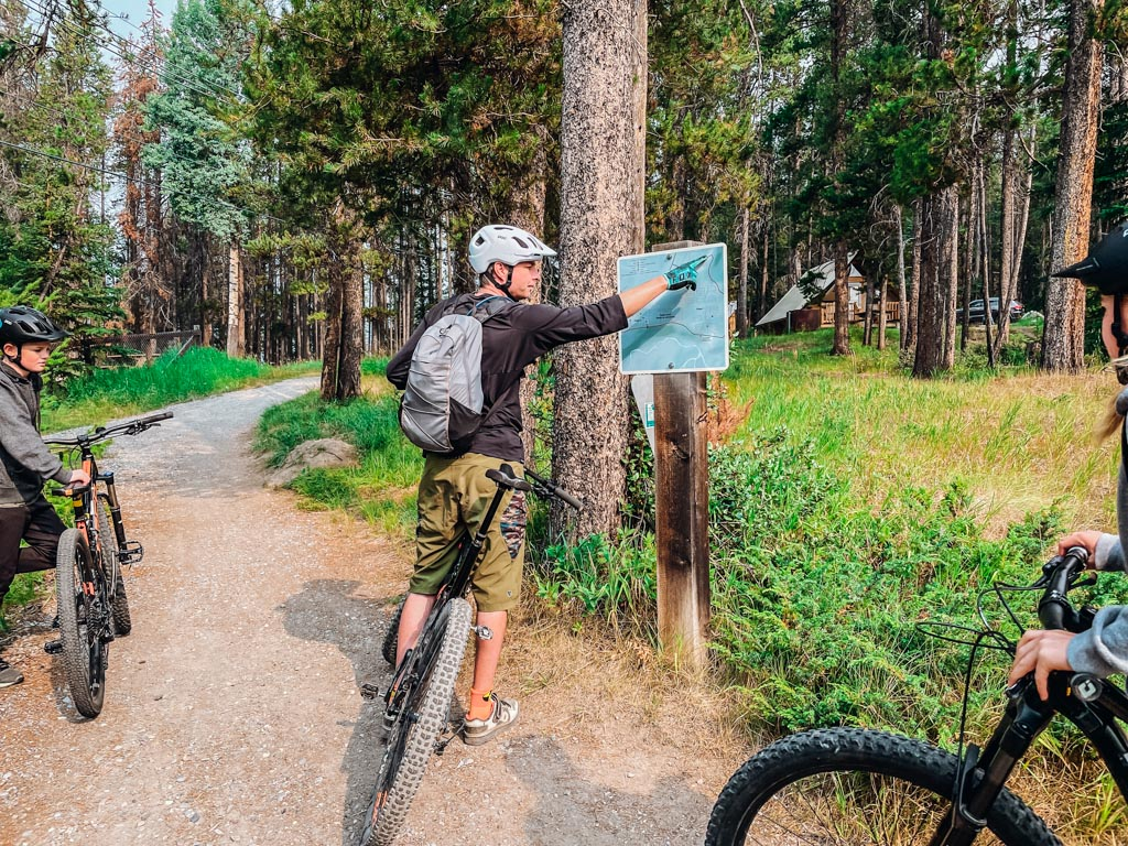 tour leader pointing to mountain biking map on a post