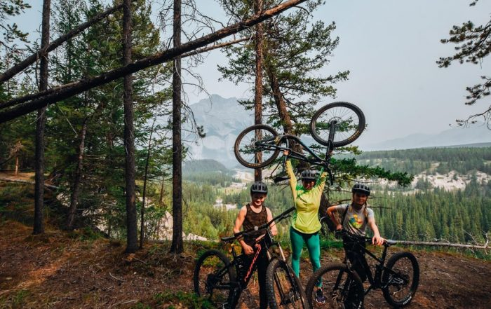 woman holding mountain bike above her head in forest with kids