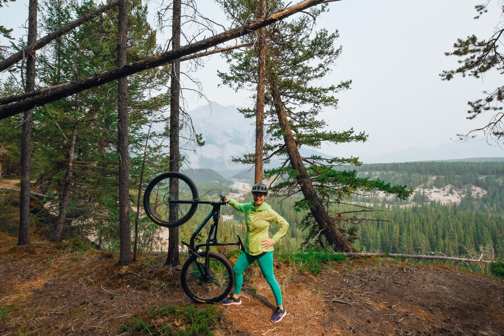 woman standing next to her mountain bike and holding it up with one hand