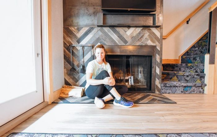woman sitting in front of stone fireplace at tunnel mountain resort