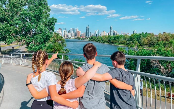 four kids with linked arms overlooking the bow river in calgary