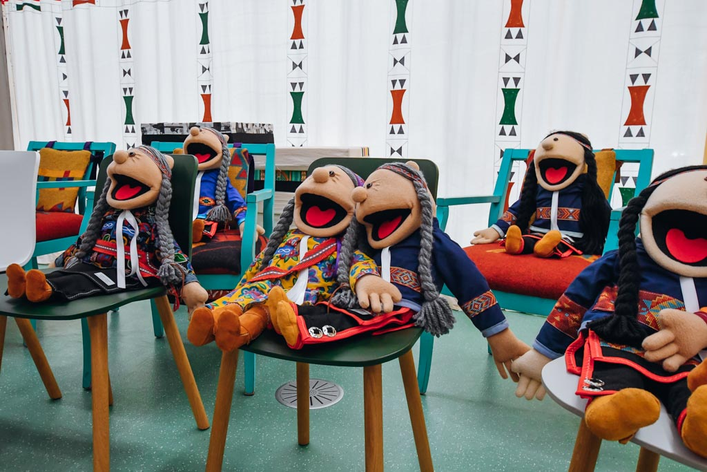 puppets sitting on chairs in a classroom