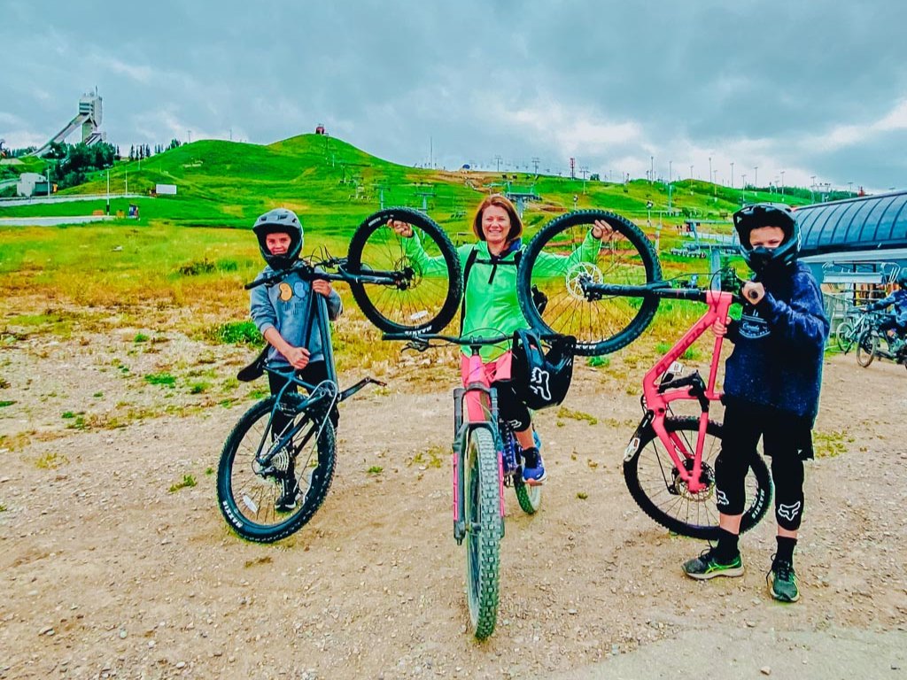 adult and two kids holding up their mountain bikes in front of the chairlift at WinSport Calgary