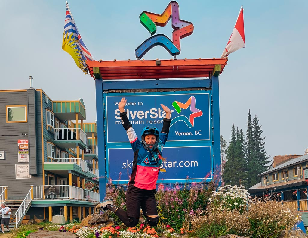 woman wearing mountain biking gear jumping in front of silverstar mountain sign