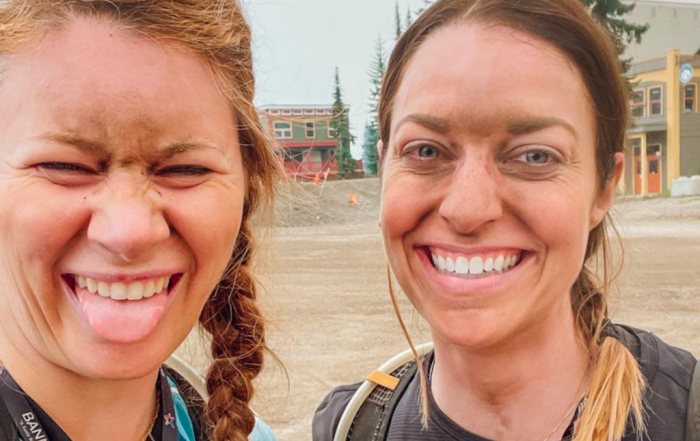 two woman covered in dust and dirt after their mountain biking course